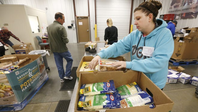 In this file photo, volunteer Cienna Bridges repackages lunch meat at the Ozarks Food Harvest. Last week Charity Navigator, the leading evaluator of nonprofits in the nation, gave Ozarks Food Harvest a 100 percent score for its transparency and financial accountability.