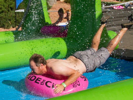St. George residents slide down 100 East during the Slide the City event Saturday, June 4, 2016.