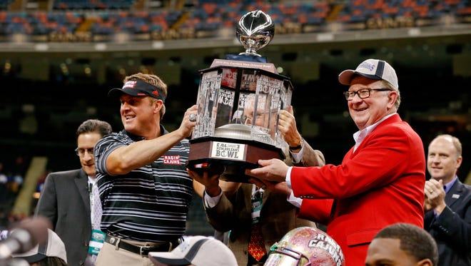 UL coach Mark Hudspeth (striped shirt) celebrates following a win over Nevada at the 2014 New Orleans Bowl. The Cajuns had to forfeit their 2011 and 2013 bowl wins following an NCAA investigation.