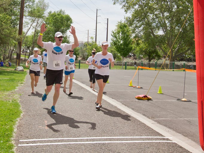 Participants run across the finish line during the