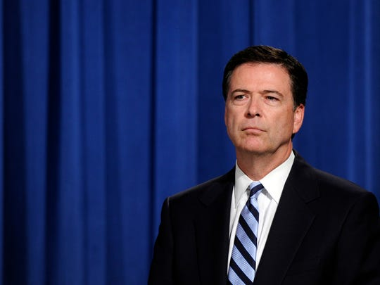 FBI Director James Comey listens during a news conference announcing a deal between the U.S. government and French bank BNP Paribas at the Justice Department in Washington, Monday, June 30, 2014. The U.S. government and French bank BNP Paribas have agreed to a settlement over alleged sanctions violations that would require the bank to plead guilty, pay almost $9 billion in penalties and face other sanctions. (AP Photo/Susan Walsh)