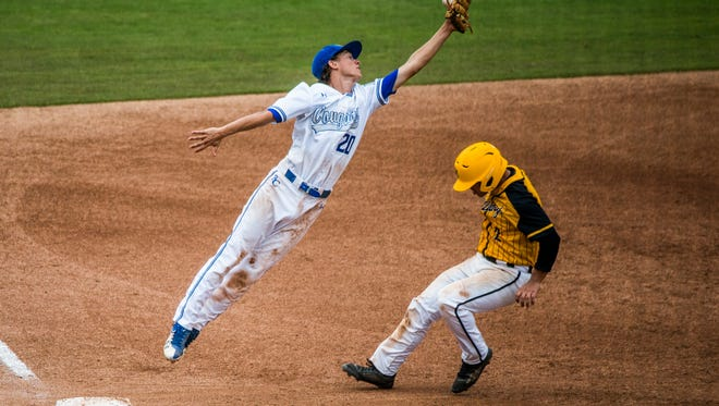 """Barron Collier sophomore Connor Phelan misses the ball and Merritt Island senior Ricardo """"RJ"""" Diaz makes it to third base during the class 6A state semifinal at Hammond Stadium in Fort Myers on Wednesday, May 30, 2018."""