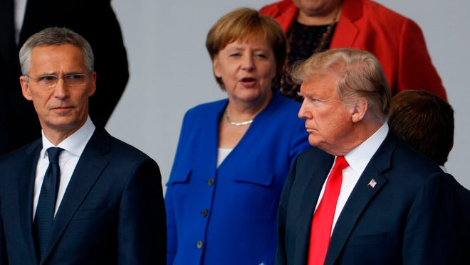 """NATO Secretary General Jens Stoltenberg, German Chancellor Angela Merkel and President Donald Trump talk during a """"family photo"""" ahead of the opening ceremony of the NATO summit in Brussels Wednesday."""