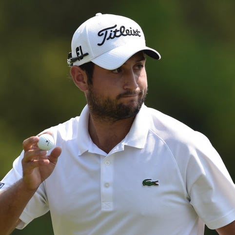 Alexander Levy of France throws his ball after making a birdie putt during the third round of the Volvo China Open golf tournament in Shanghai.