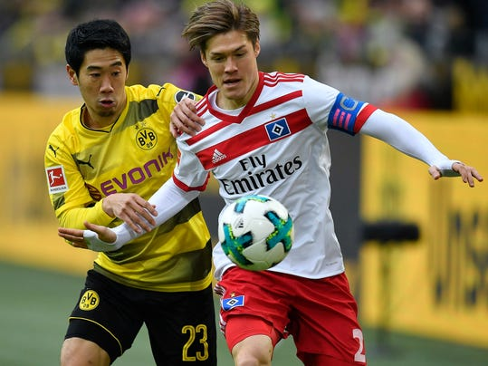FILE - In this Feb. 10, 2018, file photo, Dortmund's Shinji Kagawa, left, and Hamburg's Gotoku Sakai challenge for the ball during the German Bundesliga soccer match between Borussia Dortmund and Hamburger SV in Dortmund, Germany. While established international players like Shinji Kagawa and Keisuke Honda should play a big role on Japan's World Cup squad, coach Vahid Halilhodzic has indicated that many spots remain open and it's time for the next generation to step up. (AP Photo/Martin Meissner, File)