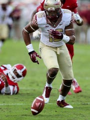 Linebacker Jacob Pugh (16) recovers a fumble by N.C. State quarterback Jacoby Brissett (12), left, as the Florida State Seminoles beat the NC State Wolfpack 56-41at Carter Finley Stadium in Raleigh, NC, on Saturday.