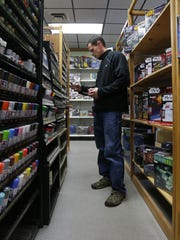 Mark Roth, of Darboy, looks for a particular red paint to use for models while shopping at Galaxy Science and Hobby in Appleton.