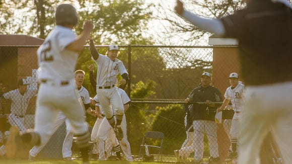 Dallastown players react as Nick Parker  comes home to score the winning run in the seventh inning of Tuesday's YAIAA championship against Northeastern at New Oxford High School.