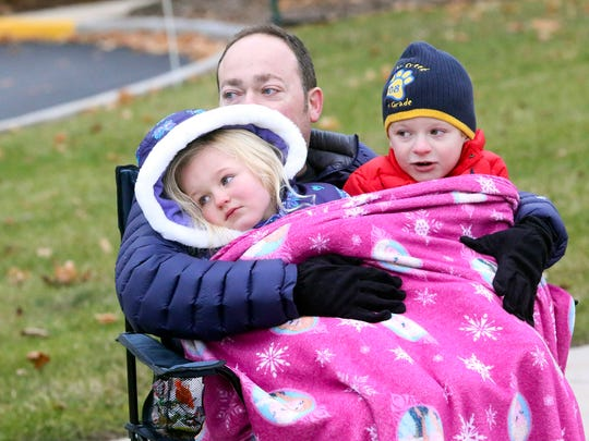 Matt Thompson, and his children, Abby (left) and Ashton, watch the New Berlin parade make its way along National Avenue in 2016.