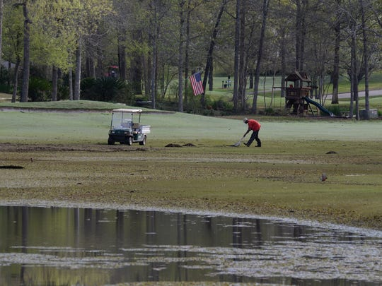 A groundsman cleans up some of the damage to a fairway