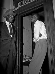 In this Sept. 29, 1955, file photo, Willie Reed, right, a witness in the Emmett Till murder case in Mississippi, stands outside the door of his apartment in Chicago under guard by Detective Sherman Smith.