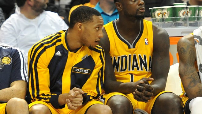 Pacers' Evan Turner and Lance Stephenson sit on the bench as the game winds down in the fourth quarter March 31, 2014.