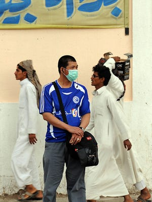 A foreign worker living in Riyadh wears a mask on a main street in the Saudi capital on April 29, 2014,  to protect against Middle East respiratory syndrome, aka MERS.