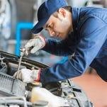 Auto mechanic working on a car.