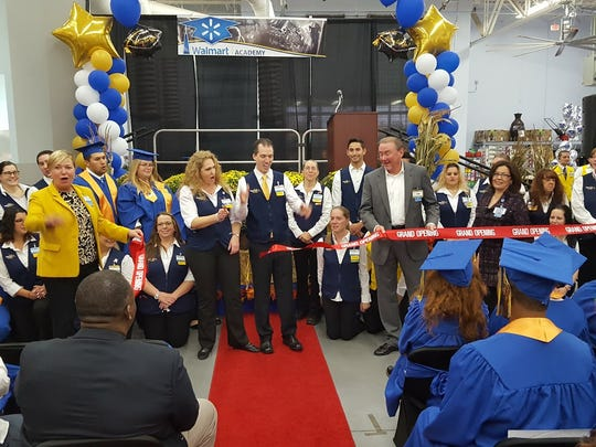 Walmart regional manager Thomas Underwood (right in suit) and others cut the ribbon as they celebrate the grand opening of the training academy at the Walmart store in Williamstown on South Blackhorse Pike. The training academy is the retail giant's first in New Jersey and will be among 200 across the country. There were 50 hourly supervisors and department managers that graduated from the academy on Thursday morning.