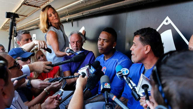 Chicago Cubs reliever Aroldis Chapman, center, listens to a question as he meets reporters before a baseball game between the Chicago White Sox and Cubs Tuesday, July 26, 2016, in Chicago.
