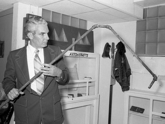 "Clay Davis, deputy warden at Brushy Mountain State Prison, displays the pipe ""ladder"" that James Earl Ray and six other inmates used to scale the prison wall on June 11, 1977."
