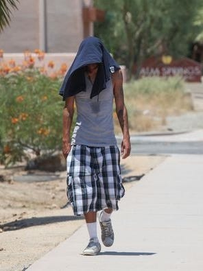 A man uses a shirt to shield himself from the sun on June 20, when temperatures reached 122 degrees in Palm Springs. It was one of four days to have temperatures that high.