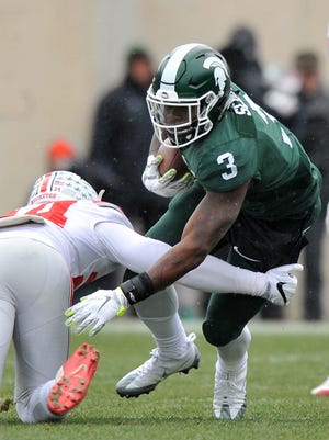 Michigan State's LJ Scott runs through a tackle in the first half Saturday.