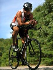 Triathlete Ken Pagliughi trains on his bike, Monday,
