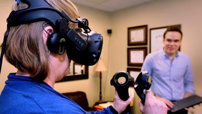 Kristin Evans, a detox therapist and clinical social worker at JourneyPure in Murfreesboro, goes through a tutorial of the virtual reality gaming system that Noah Robinson, a clinical psychology doctoral student at Vanderbilt University, uses to help rehab patients on Feb. 22, 2018. Robinson, who monitors what Evans is experiencing, tries to encourage all the therapists to try out the program so they can recommend the therapy to their patients.