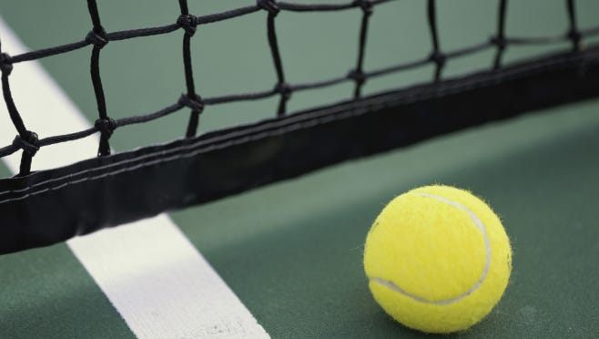 Close-up of a tennis ball and net on a tennis court