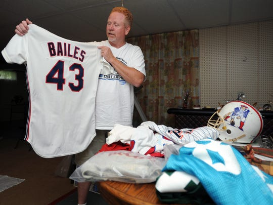 Bruce Caplinger holds up one of his jerseys Wednesday. Caplinger has a large collection of jerseys, cards, equipment and other pieces from Ross County athletes.