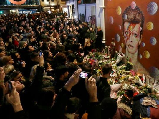FILE - In this Monday, Jan. 11, 2016 file photo people gather next to tributes placed near a mural of British musician David Bowie by artist Jimmy C, in Brixton, south London. Bowie, the other-worldly musician who broke pop and rock boundaries with his creative musicianship, nonconformity, striking visuals and a genre-spanning persona he christened Ziggy Stardust, died Jan. 10, 2016.
