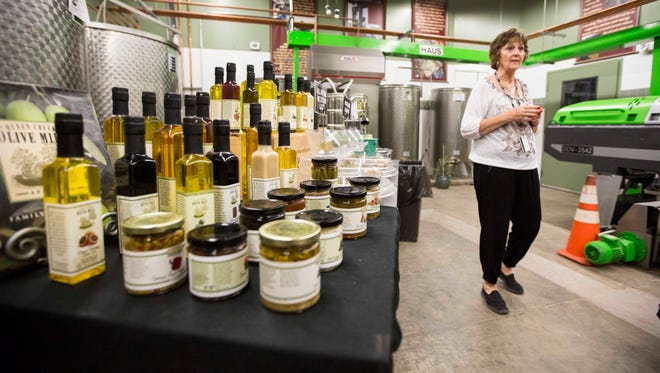 Bonnie Gordon guides a tour of the Queen Creek Olive Grove during the first annual Garlic Festival, September 20, 2014, Queen Creek, Ariz. During the presentation Gordon stated that it takes 100 pounds of olives to produce 1 gallon of olive oil.