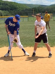 A corning Hawks football member instructs a Royals Little League Challenger Division player.