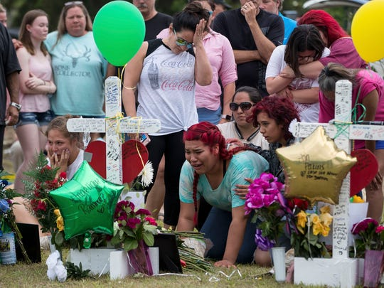 A girl becomes emotional as she kneels in front of a cross at a makeshift memorial outside Santa Fe High School, May 21, 2018.