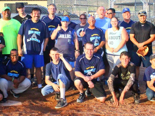 Law enforcement officers and members of the Special Olympics softball team, the Otero County Lions, pose for a picture after their annual scrimmage Saturday night.