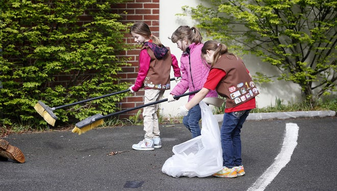 Brownie Troop 4089 members clean the parking lot outside the Quicker Printer building on Gray Street in Elmira during the 2016 Downtown CleanUp.