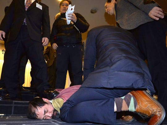 This handout photo taken and released on March 5, 2015 by South Korean local newspaper the Asia Economy Daily shows a man (bottom left corner) who attacked US ambassador to South Korea Mark Lippert, being detained by police at the Sejong Cultural Institute in Seoul. Lippert was slashed on his face and arm by a blade-wielding assailant shouting anti-war slogans in an attack in Seoul on March 5, police and reports said.