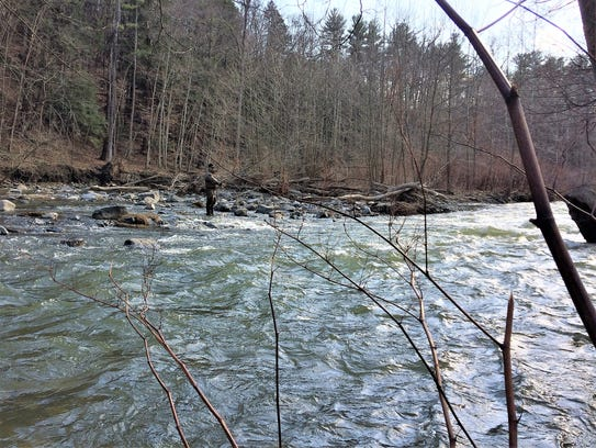 A fly fisherman casts into the rapids at the bottom