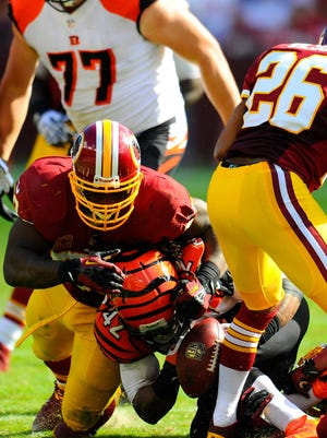 Washington Redskins inside linebacker London Fletcher (59) hits Cincinnati Bengals running back BenJarvus Green-Ellis (42) causing him to fumble the ball during the third quarter at FedEx Field. The Bengals defeated the Redskins 38-31. Mandatory Credit: Dale Zanine-USA TODAY Sports
