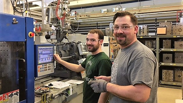 Jordan Abt and Volker Dettlaf set up the press for a new order at Nicolet Plastics in Mountain.