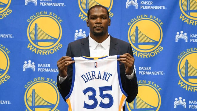 Kevin Durant poses for a photo with his jersey during a press conference after signing with the Golden State Warriors at the Warriors Practice Facility.
