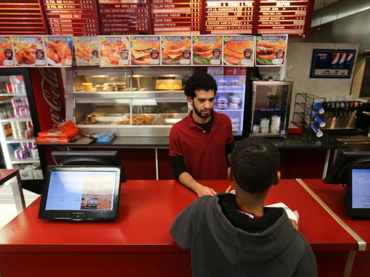 Mustafa Gomaa takes an order from a customer at Kennedy Fried Chicken on North Market Street in Wilmington Tuesday.
