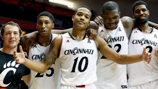 Bearcats guard Troy Caupain (10) celebrates with teammates after Wednesday's win against Houston.