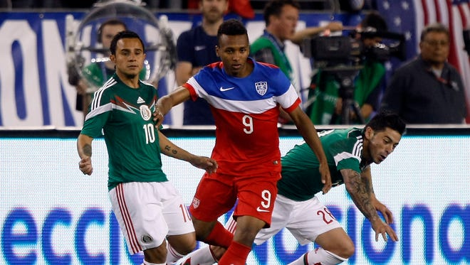 U.S. Julian Green (9) battles for the ball with Mexico defenders during the second half of an international friendly soccer match April 2, 2014, in Glendale, Ariz.
