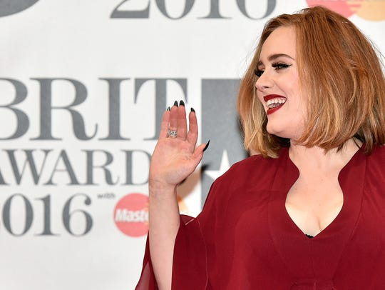 Adele poses on the red carpet after arriving to attend