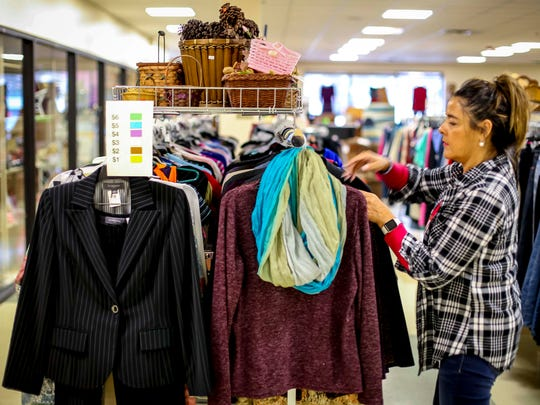 Store manager Irma Donan sorts the clothes racks at theRenew Resale Shop Tuesday, April 3, 2018, in the Park Fair Mall in Des Moines, Iowa.