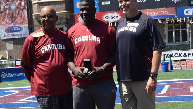 South Carolina junior Josh Awotunde, center, poses with his medal after winning the college discus at the Penn Relays on Friday.
