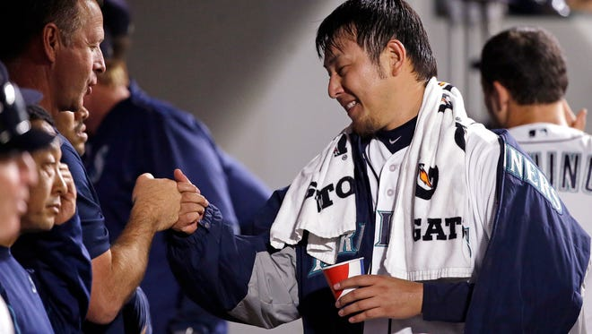 Seattle Mariners starting pitcher Hisashi Iwakuma is greeted in the dugout after pitching seven innings of a baseball game against the Detroit Tigers Monday, Aug. 8, 2016, in Seattle. (AP Photo/Elaine Thompson)