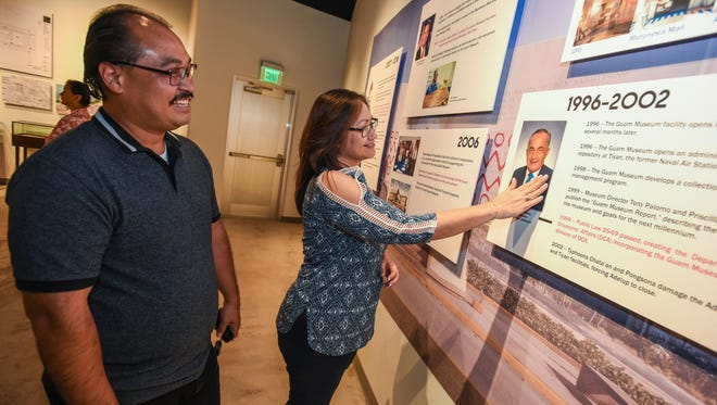 "Chamorro Affairs employee Jennifer Paulino reaching out to touch an image of former Guam historian and former Guam Museum director, Antonio ""Tony"" Palomo, as she an co-worker Jeff San Nicolas tour the ""I Hale'ta: Desde Åntes esta I Mamaila'"" exhibition at the facility in Hagåtña, named after Palomo, on Friday, Nov. 4, 2016. A soft opening was held for first floor of the Antonio ""Tony"" Palomo Guam Museum and Chamorro Educational Facility, also known as the Guam Museum, and an exhibit which chronicles the history of the Guam Museum from 1926 to 2016."