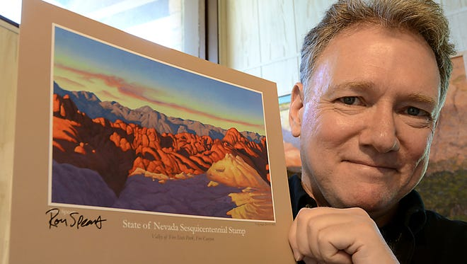 Reno artist Ron Spears holds a print showing his winning entry for the Nevada Sesquicentennial stamp show Fire Canyon in the Valley of Fire.