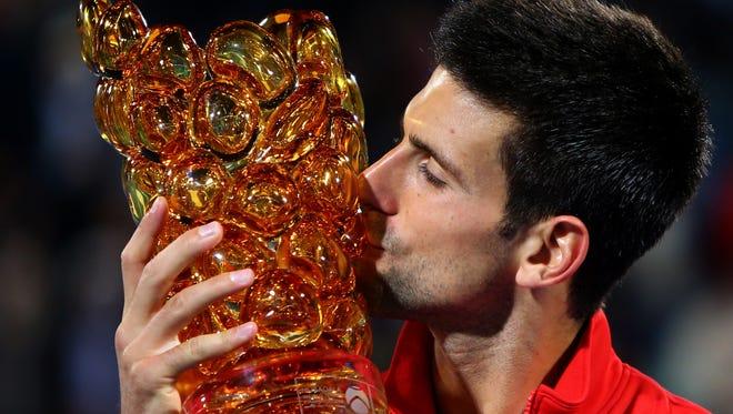 Serbia's Novak Djokovic kisses his trophy after winning of the Mubadala World Tennis Championship in Abu Dhabi againts Spain's David Ferrer.