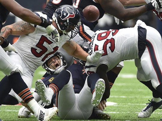 Houston Texans outside linebacker Whitney Mercilus (59) forces Chicago Bears quarterback Jay Cutler, center, to fumble during the Sept. 11 game in Houston. The Texans and Minnesota Vikings are among the teams with the top records in the NFL winning with defense first and quarterback second.