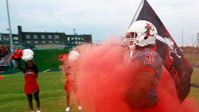 East Nashville's Anthony Collier carries a flag as he walks through smoke before a game against Maplewood.